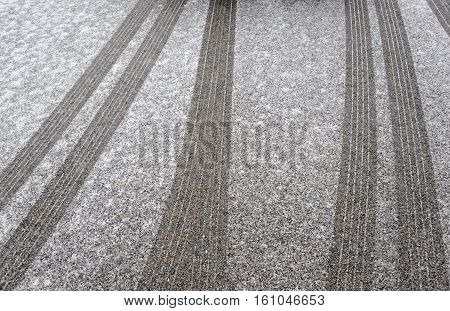 cars and tire tracks on the driveway in snowing day