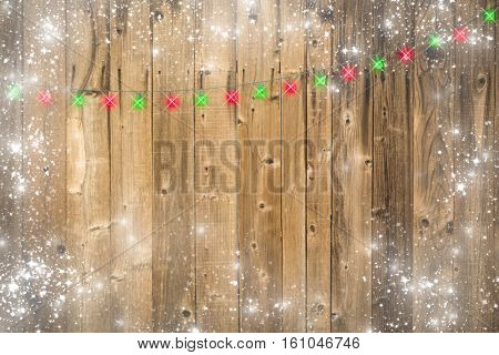 Lustrous Wooden Background with Bright Green and Red Christmas Lights and Snowy Border.