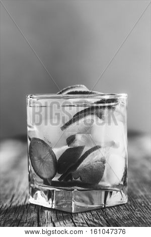 refreshing drink with green lemon and ice close up black and white photo