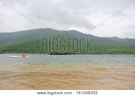 Vietnam, December 8, 2016. views of the sea and the mountains of Vietnam, near the shore of shallow water through which you see the yellow sand, greenish sea water people bathe, swim, kayak, far away are the ships with the flag of Vietnam, mountains cover