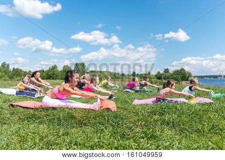 Fit women doing exercises stretching hamstrings fitness class in parkland.