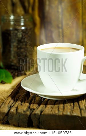 Coffee drink in white coffee cup and black coffee beans and background
