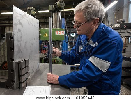 Saint-Petersburg Russia - November 16 2016: Turner miller makes measurements of sheet metal using a planer in the workshop of a machine-building factory machining