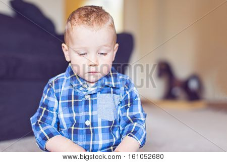 adorable toddler with blue eyes being upset and unhappy at home toned image