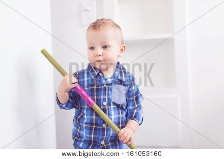 adorable toddler with blue eyes helping with chores sweeping the floor at home