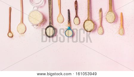 Quinoa seeds in different spoons and open glass jar over light pink background, top view, copy space. Superfood, healthy eating, dieting, clean eating, detox or vegetarian food concept