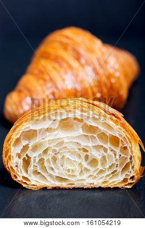 close-up of two croissants one cut in half with inside texture visible delicious french pastry