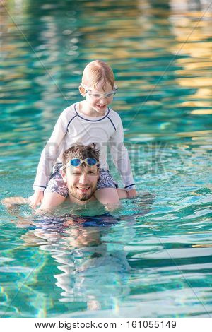 young father and smiling son enjoying and playing together in the pool kid sitting on father shoulders