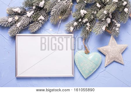 Empty silver frame and Christmas decorations on blue textured background. Place for text. Mock-up for design.