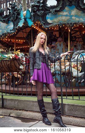 Fashion beauty model woman posing on carousel in amusemet park.