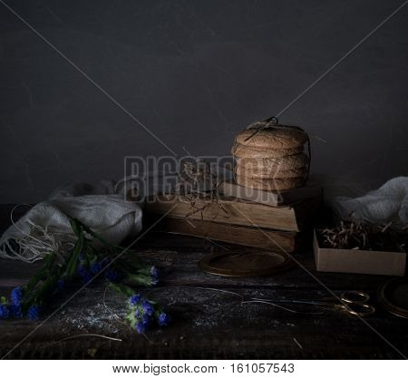 still life. old books, cornflowers, cakes, drapery on a wooden table