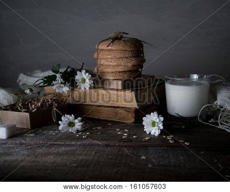 vintage. old books, a glass of milk, cakes, drapery on wooden table