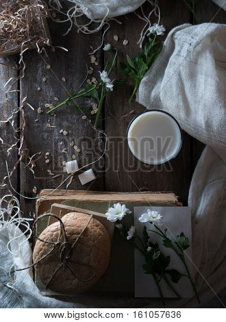 still life. old books, a glass of milk, cakes, drapery on a wooden table. top view