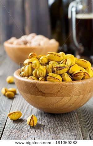 Salted pistachios with saffron and glass of beer on old wooden background. Rustic style. Selective focus.