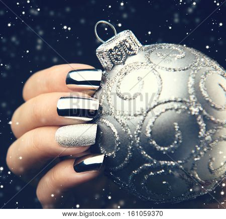 Christmas Nail art manicure idea. Winter Holiday style bright Manicure Design. Christmas decorations, snowflakes. Nail Polish. Beauty hands. Trendy Stylish Silver and Blue Colorful Nails, Nailpolish.