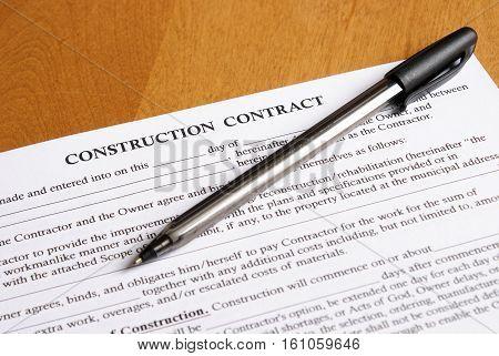 Closeup view of a new contract deal arranged on the desktop with a pen for writing and signing.