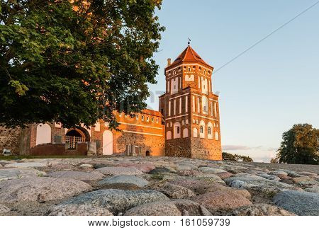 Mir, Belarus - August 24,2016:  Fortress tower of a medieval castle in the town of Mir in Belarus and the pavement of cobblestones on a background of blue sky