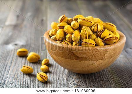 Salted pistachios with saffron in a bamboo plate. Selective focus.