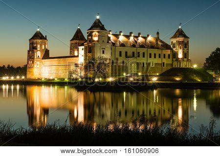 Mir, Belarus - August 28,2016:  Illuminated medieval castle in the Belarusian town of Mir with reflection in a lake on sunset background