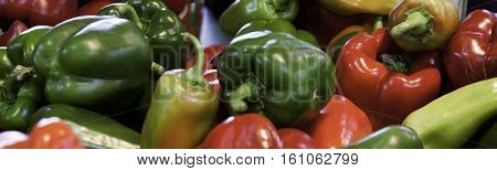 Wide angle of red and green peppers at the outdoor/indoor Jean-Talon Market in Montreal, Quebec, on a bright day in September.