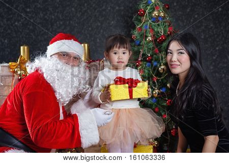 Santa Claus and mother with your child dress. Christmas Scenes. The Child holding gift box Packed