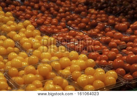 Angled view of rows of yellow and red cherry tomatoes in small containers at the outdoor/indoor Jean-Talon Market in Montreal, Quebec, on a bright day in September.