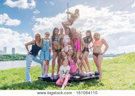 Full length portrait of women standing near pylon Pole sport