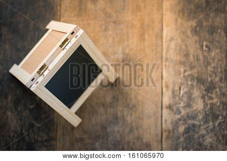 Blackboard in wooden frame on wooden background