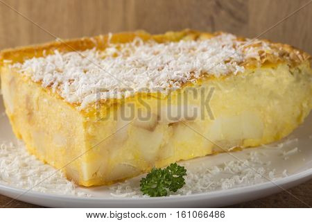 Baked polenta with potatoes cheese and smashed eggs on plate