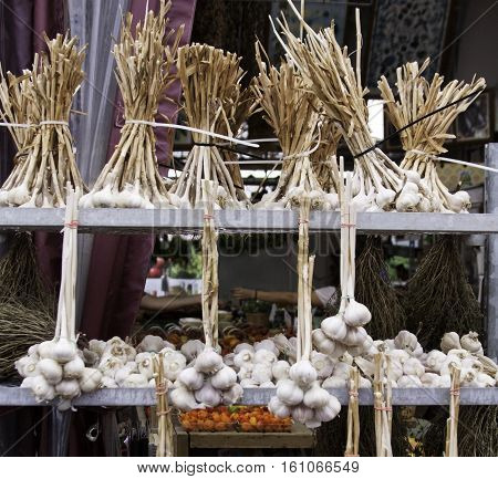 Stacked rows of fresh braided garlic displayed in front of an store at the outdoor/indoor Jean-Talon Market in Montreal, Quebec, on a bright day in September. You can see two arms reaching to exchange payment.