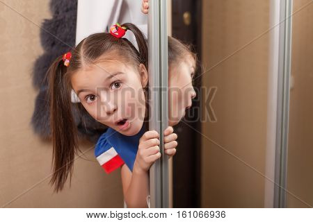 Little girl looks out of the closet.