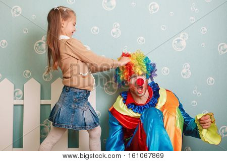 Little girl pulls clown hair.