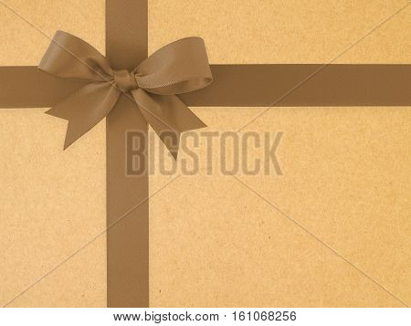 dark brown ribbon with bow on brown paper texture background, simple earth tone color decorate for gift box and greeting card