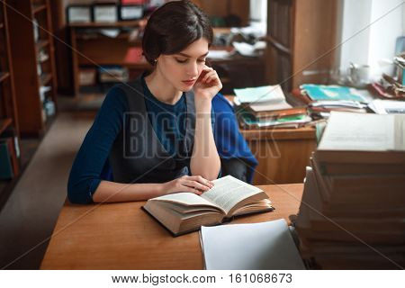 Portrait of clever student in university library.