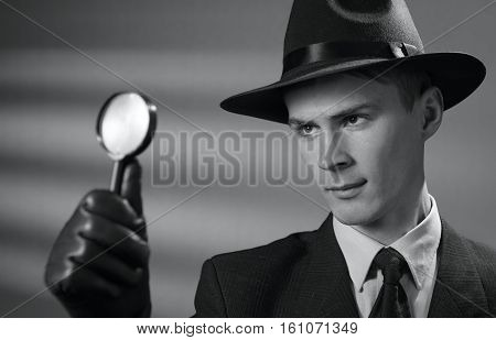 Young Vintage Detective Holding A Magnifying Glass