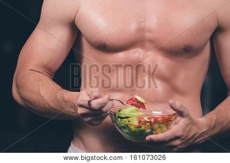 Shaped and healthy body building man holding a fresh salad bowl, shaped abdominal, isolated on dark background