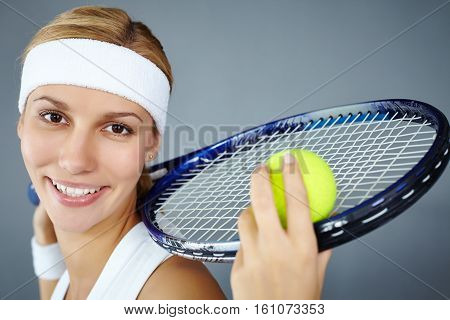 Portrait of a smiling girl with tennis racket in studio