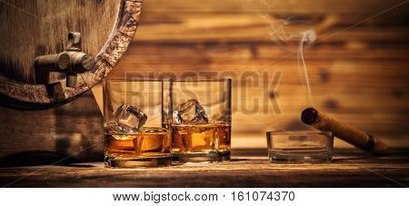 Two glasses of whiskey with ice cubes served on wooden planks with keg. Vintage countertop with highlight and glasses of hard liquor