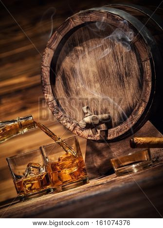 Pouring whiskey from bottle to two glasses with ice cubes, served on wooden planks. Vintage countertop with keg and glasses of hard liquor