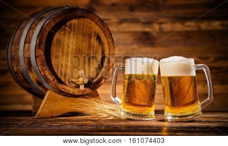Two glasses of lager with old wooden keg, copyspace for text
