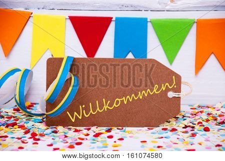 Brown Label With German Text Willkommen Means Welcome. Party Decoration Like Streamer And Confetti. White Wooden Background. Greeting Card For Celebrations