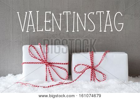 German Text Valentinstag Means Valentines Day. Two White Christmas Gifts Or Presents On Snow. Cement Wall As Background. Modern And Urban Style.