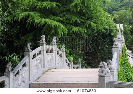 Chinese lions topping the posts of a stone bridge within Taiping Palace in Qingdao in Shandong province China.
