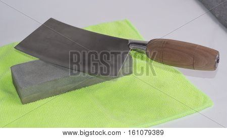 Chinese chef's knife and sharpening stone on a yellow background