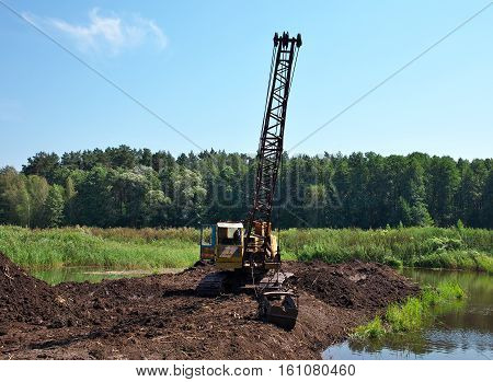 Excavator developing the peat on the swamp on a sunny day