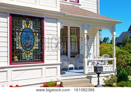 Historical white American house porch with stain glass window. Port Townsend WA.