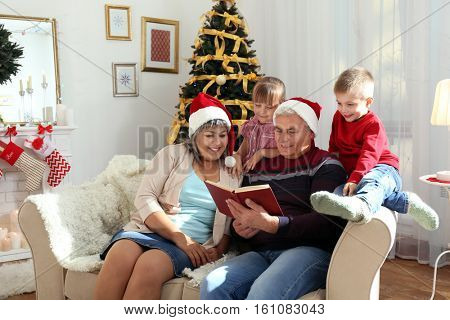 Elderly couple reading book to their grandchildren in living room decorated for Christmas