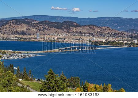 A view of the bridge over Okanagan Lake between West Kelowna and Kelowna Brititsh Columbia Canada with a view of the Kelowna skyline and a marina in the foreground