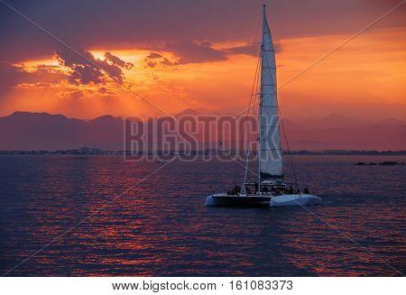 Colorful sunset. Dramatic and Atmospheric landscape. Costa Brava Spain. Seacoast. Seascape with sailboat. Tourist catamaran. Sunset on the coast Amadrava.