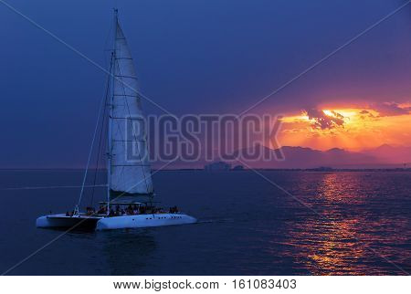 Colorful sunset. Dramatic and Atmospheric landscape. Costa Brava Spain. Seacoast. Seascape with sailboat. Tourist catamaran. Sunset on the coast Almadrava. Catalonia